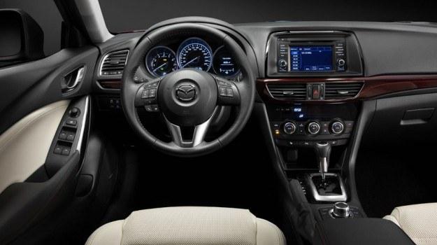 Kokpit ma architekturę znaną z modelu CX-5, z zegarami w tubach i 5-calowym ekranem pokładowej telematyki. Nowością jest pas ciemnoczerwonego tworzywa, biegnący przez front deski rozdzielczej. /Mazda