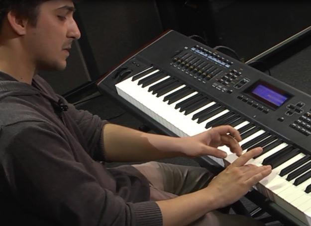 Konrad Wantrych pokazuje właściwe ułożenie dłoni na instrumencie klawiszowym /