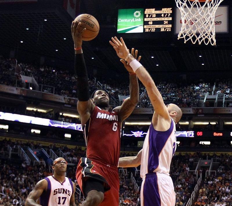 Koszykarz Phoenix Suns Marcin Gortat próbuje zablokować LeBrona Jamesa z Miami Heat /AFP