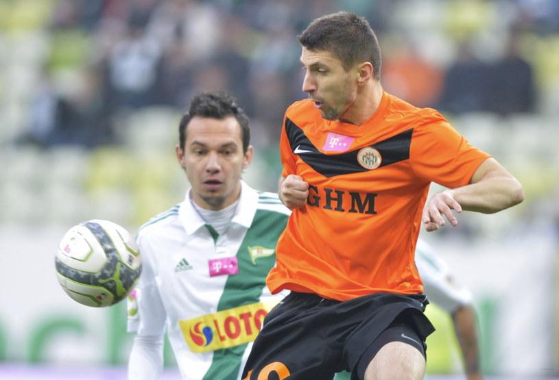 Krzysztof Bąk (z lewej) walczy o piłkę z Maciejem Małkowskim /Fot. Adam Warżawa /PAP
