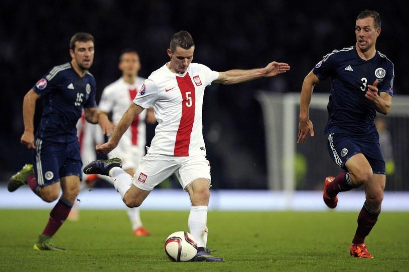 Krzysztof Mączyński (w białym stroju) w meczu reprezentacji Polski ze Szkocją /AFP