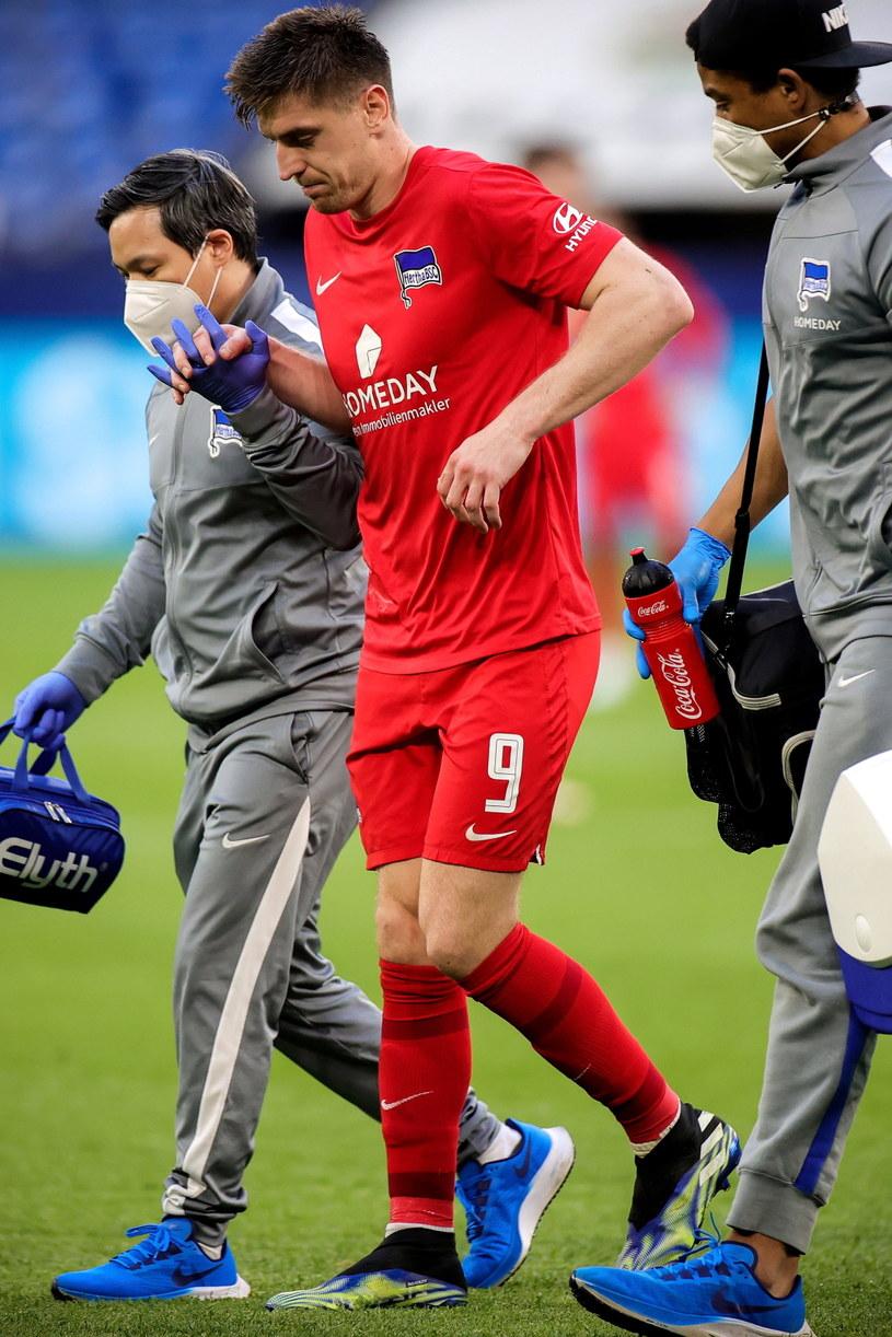 Krzysztof Piątek schodzi z boiska z grymasem bólu /PAP/EPA