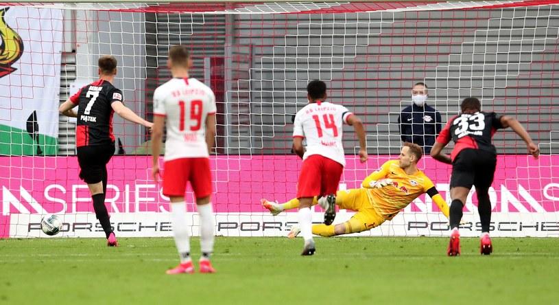 Krzysztof Piątek skutecznie wykonuje rzut karny w meczu z RB Lipsk /AFP