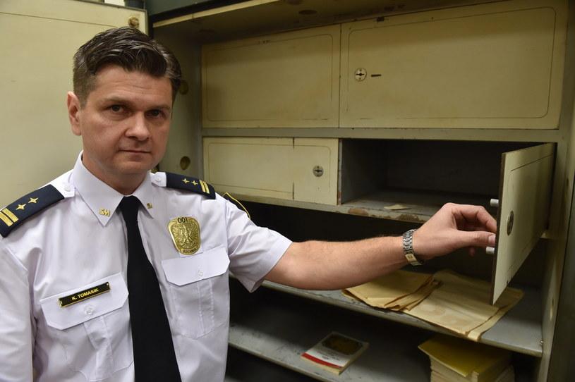 Krzysztof Tomasik prezentuje przedmioty znalezione w zabytkowej kasie /Jacek Bednarczyk /PAP