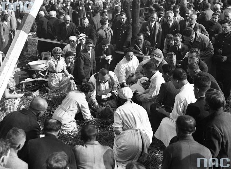 Ksiądz otoczony tłumem ludzi udziela ostatnich sakramentów jednej z ofiar katastrofy /Z archiwum Narodowego Archiwum Cyfrowego