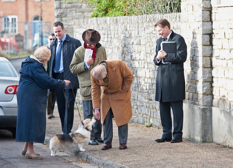 Książę Karol zatrzymujący się, by pogłaskać psa podczas wizyty w Poundbury /Getty Images