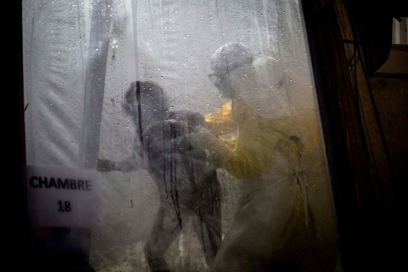 Lekarz pomaga pacjentowi z podejrzeniem zakażenia wirusem ebola w dotarciu do łóżka. Zdjęcie wykonano w Demokratycznej Republice Konga w 2018 roku. /JOHN WESSELS /AFP