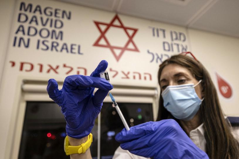 Lekarz z izraelskiej służby ratunkowej przygotowuje strzał przypominający szczepionki na koronawirusa w Tel Awiwie w Izraelu /AP/Associated Press/East News /East News
