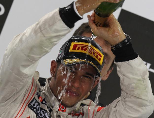 Lewis Hamilton skąpany w szampanie na podium GP Abu Zabi /AFP