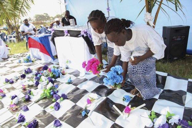 Liberyjskie dzieci upamiętniają kwiatami ofiary Eboli /PAP/EPA/AHMED JALLANZO /PAP/EPA