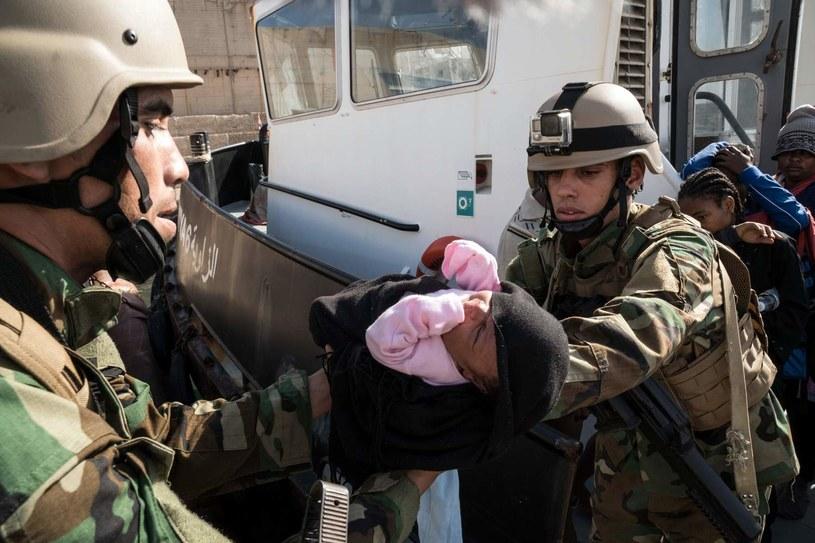 Libijscy żołnierze z dzieckiem nielegalnych migrantów, których łódź została zatrzymana niedaleko wybrzeża Libii /AFP
