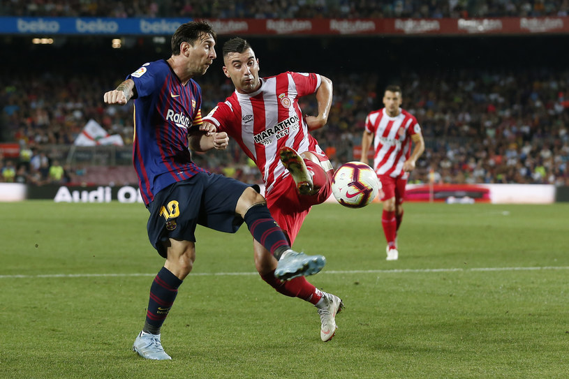 Lionel Messi (Barcelona, z lewej) w walce z Borją Garcią z Girony /AFP