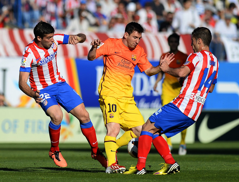 Lionel Messi osaczony przez dwóch piłkarzy Atletico Madryt /AFP