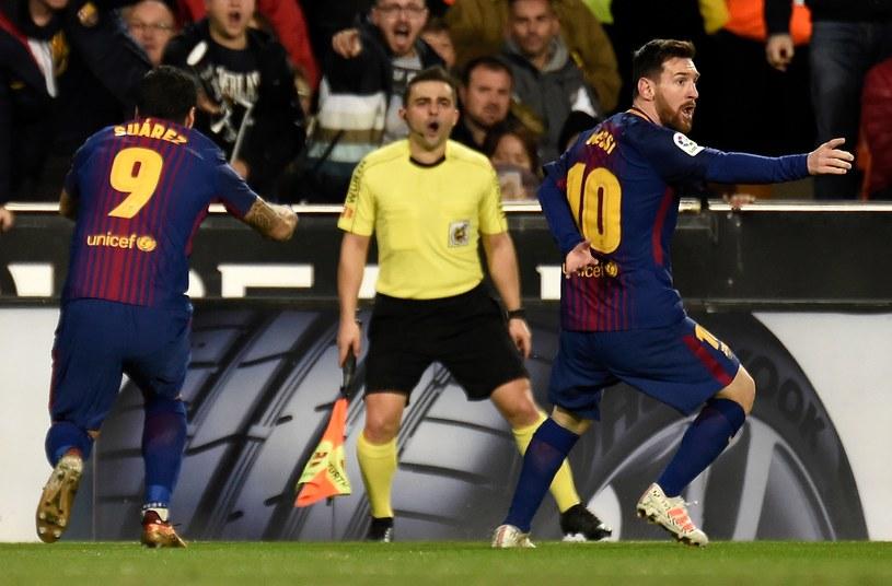 Lionel Messi (P) protestuje po nieuznanym golu w meczu z Valencią /AFP