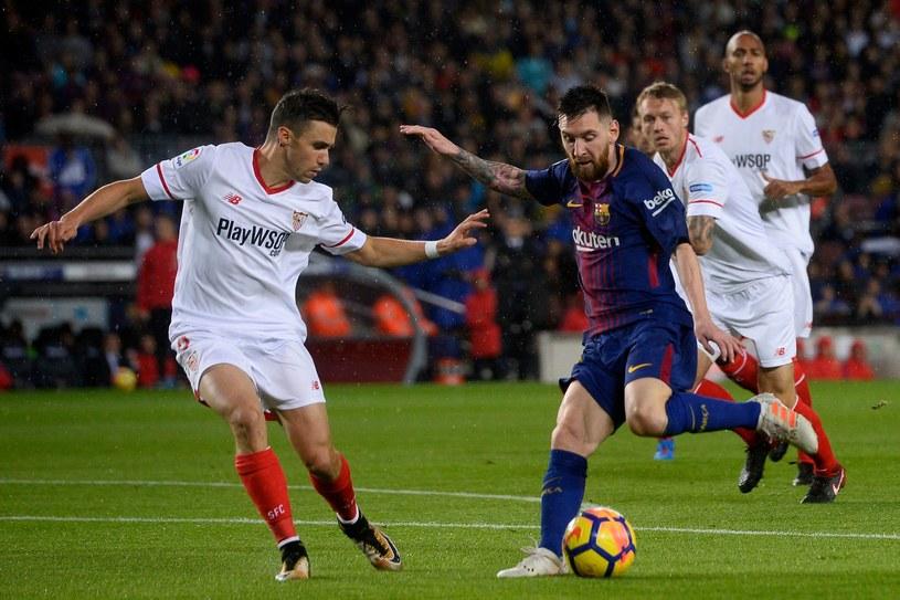 Lionel Messi (przy piłce) w meczu z Sevillą /AFP