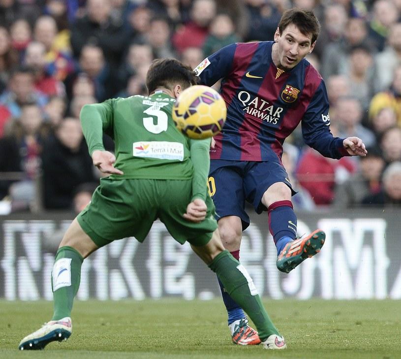 Lionel Messi strzela na bramkę Levante. Obok Tono Garcia /AFP