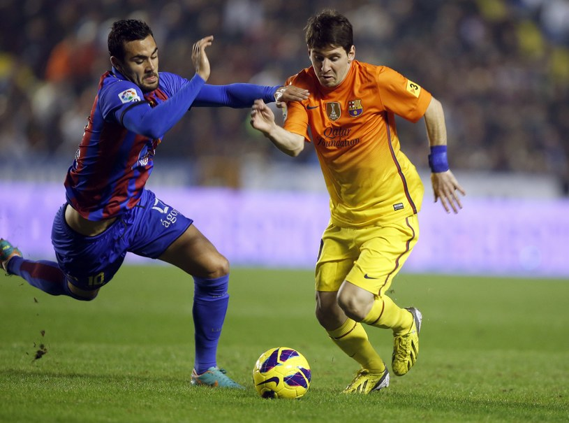 Lionel Messi ucieka pomocnikowi Levante - Vicente'owi Iborrze. /AFP
