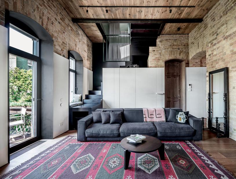 LOFT W KAMIENICY, KIJÓW. Wnętrze w zabytkowej kamienicy wcale nie musi kontynuować tradycji mieszczańskiej przytulności, by być w zgodzie z 'duchem miejsca'. Oto przykład: nowoczesny, surowy apartament któremu stara architektura, odarta z tynków, tapet, ozdobnych naleciałości – aż do gołej cegły – nadaje ton