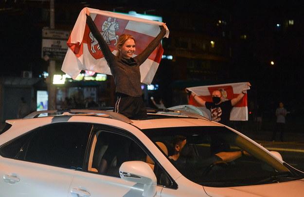 Ludzie protestujący z flagami Białorusi /YAUHEN YERCHAK /PAP/EPA