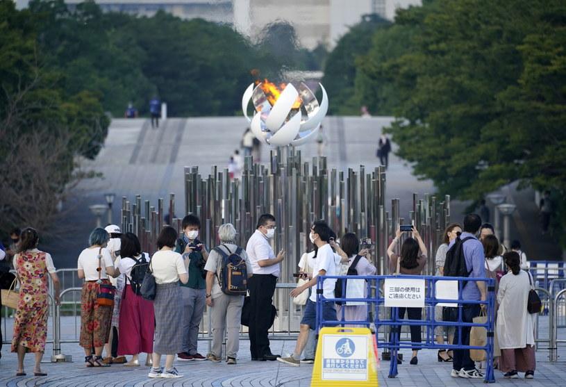 Ludzie robiący sobie zdjęcia przed zniczem olimpijskim w Tokio /FRANCK ROBICHON /PAP/EPA