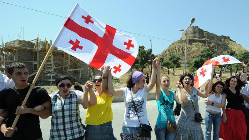 Ludzie trzymający gruzińską flagę w drugą rocznice wybuchu konfliktu z Rosją, Gori, Gruzja, zdjęcie ilustracyjne /VANO SHLAMOV /AFP
