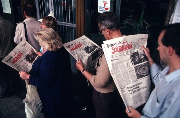 """Ludzie w kolejce czytający pierwszy numer """"Tygodnika Solidarność"""" /Chris Niedenthal /Agencja FORUM"""