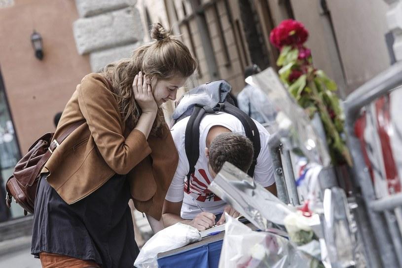 Ludzie wpisują się do księgi kondolencyjnej przed ambasadą Francji w Rzymie /PAP/EPA