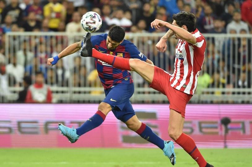 Luis Suarez (z lewej) z Barcelony oraz Stefan Savić z Atletico Madryt /AFP