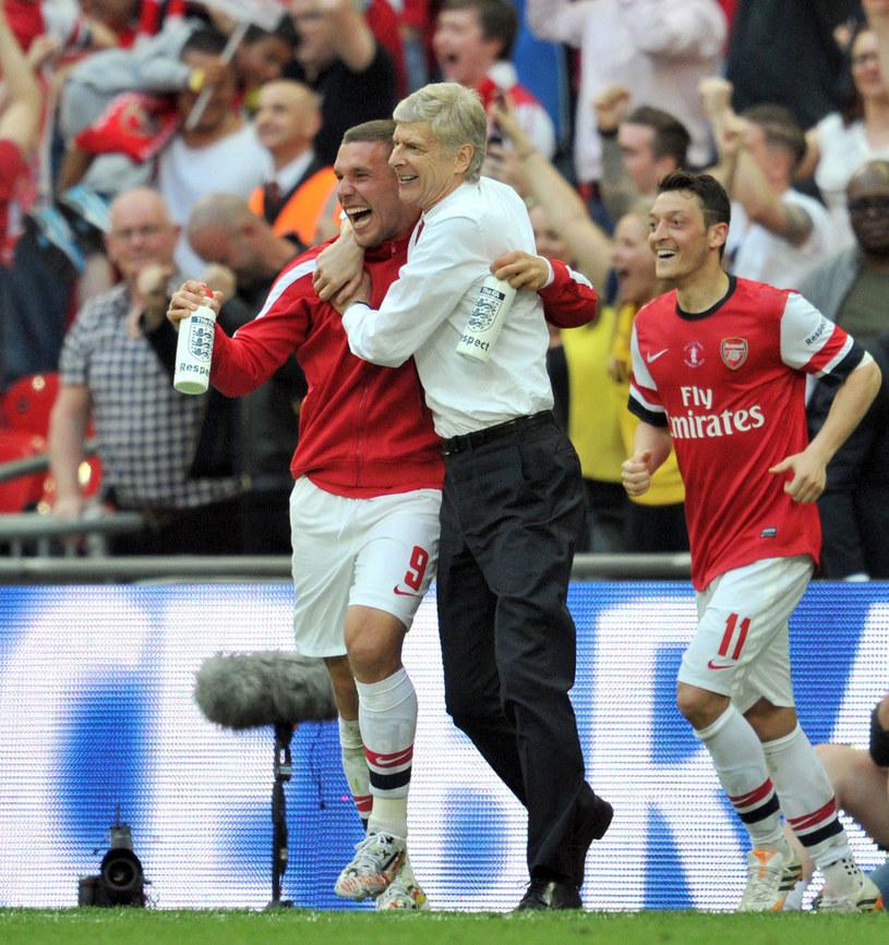 Lukas Podolski w objęciach Arsene'a Wengera po zdobyciu w maju Pucharu Anglii, z tyłu Mesut Oezil /AFP