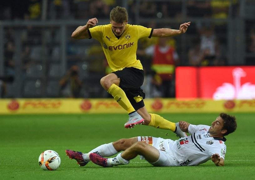 Łukasz Piszczek (na żółto) w szarży z piłką /AFP