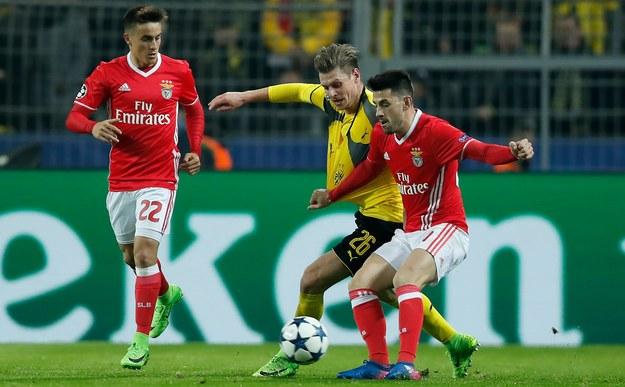 Łukasz Piszczek (w żółtej koszulce) walczy zawodnikiem Benfiki /Friedemann Vogel /PAP/EPA