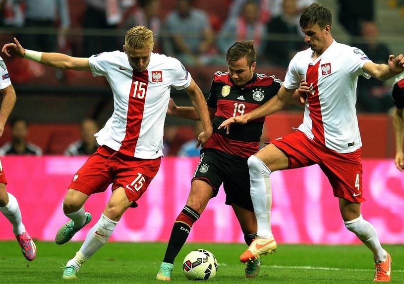 Łukasz Szukała (z prawej) walczy o piłkę z Mario Goetze podczas spotkania z Niemcami /AFP