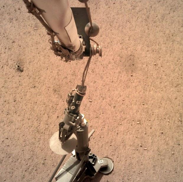 Manewr stawiania sondy termicznej z Kretem na powierzchni Marsa, sfotografowany z pomocą kamery IDC (Instrument Deployment Camera) /NASA
