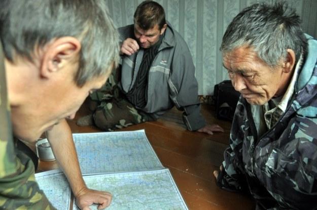 """""""Mapy' jakimi dysponowaliśmy, budziły ogromne zainteresowanie. Myśliwi z Farkowa próbują ustalić trasę naszej wyprawy"""". /arch. Projektu """"Dead Road 2013"""" /Odkrywca"""