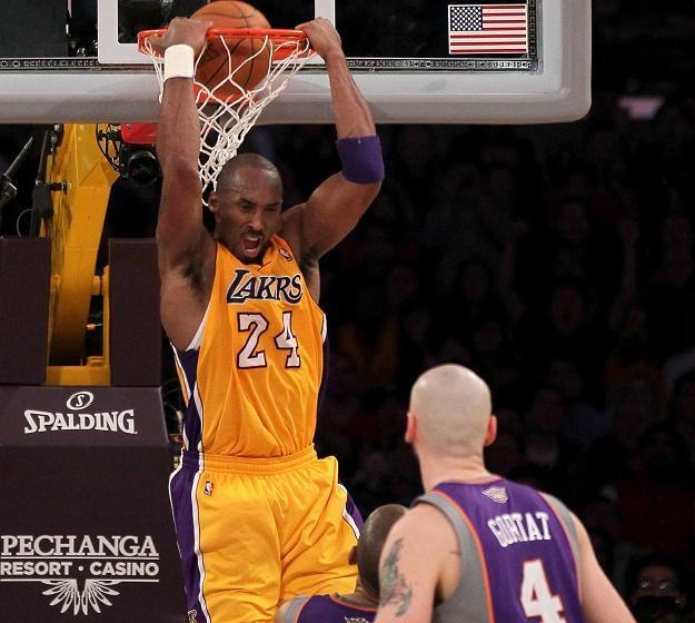 Marcin Gortat przygląda się, jak Kobe Bryant zdobywa kolejne punkty. /AFP