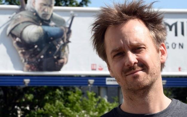 Marcin Iwiński - zdjęcie na tle bilboardu promującego grę Wiedźmin 3 /AFP