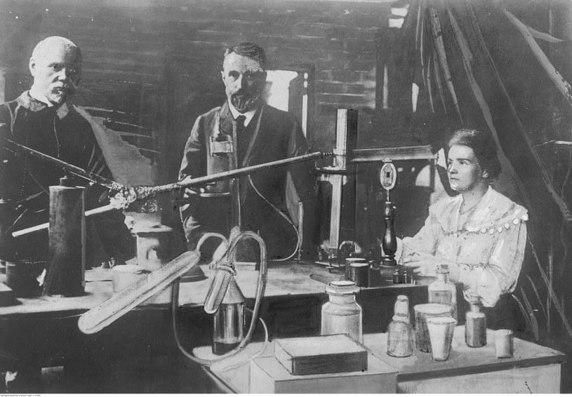 """Maria Skłodowska-Curie i jej mąż Pierre (w środku) w laboratorium (fotografia oryginalna wykonana przed 1906 rokiem, która znalazła się w zasobie """"Ilustrowanego Kuriera Codziennego"""" /Z archiwum Narodowego Archiwum Cyfrowego"""