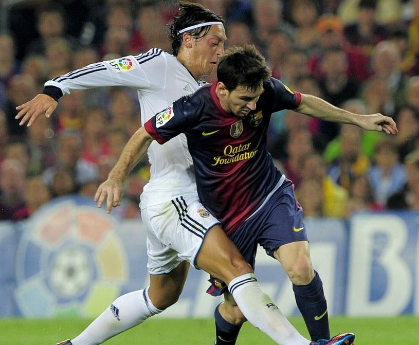 Mesut Oezil w walce z Lionelem Messim /AFP