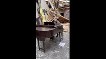 Mężczyzna gra na pianinie w zniszczonym przez tornado kościele