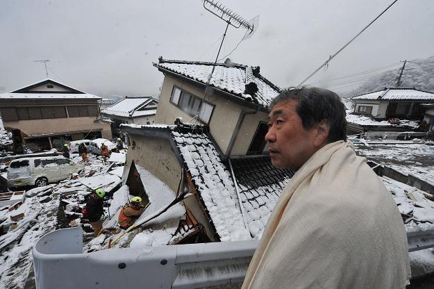 Mężczyzna obserwuje ratowników przeszukujących dom w Kamaishi /AFP