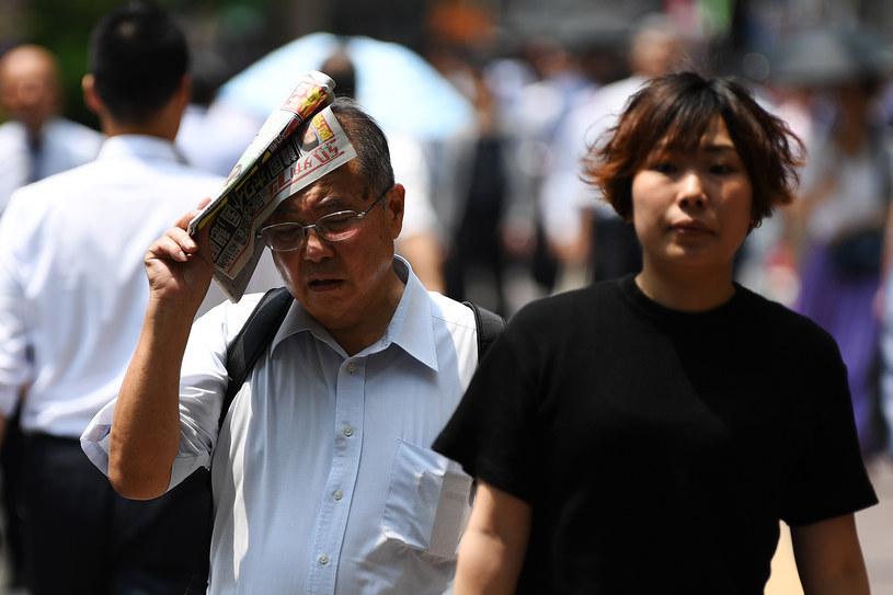 Mężczyzna osłania się od słońca gazetą podczas upału w Tokio /CHARLY TRIBALLEAU  /AFP