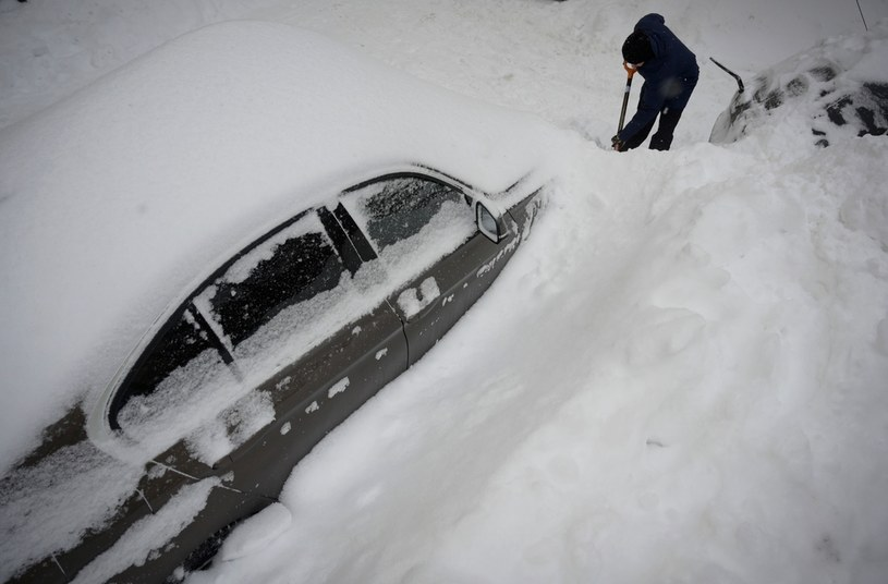 Mężczyzna próbuje odśnieżyć swój samochodów w Moskwie po potężnych opadach śniegu /Natalia Kolesnikova /AFP