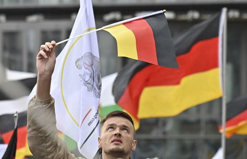 Mężczyzna trzyma niemiecką flagę na demonstracji /TOBIAS SCHWARZ /AFP