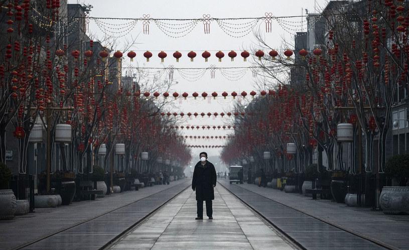 Mężczyzna w masce ochronnej na pustej ulicy w Pekinie /Kevin Frayer /Getty Images