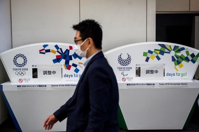"""Mężczyzna w maseczce przechodzi obok wyłączonych liczników, które odmierzały czas do rozpoczęcia igrzysk. Znajduje się na nich napis w języku japońskim: """"W trakcie dostosowywania"""". /BEHROUZ MEHRI /AFP"""