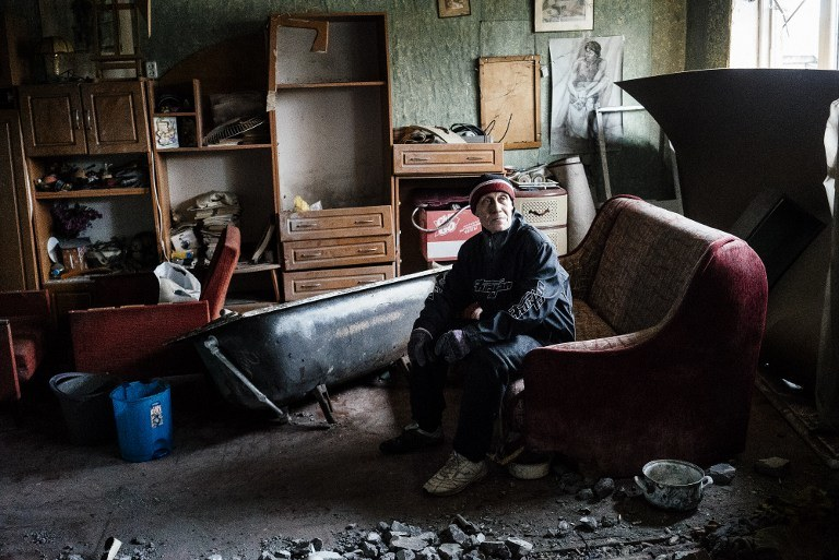 Mężczyzna w mieszkaniu zniszczonym w czasie walk, okolice Doniecka, kwiecień 2015 /DIMITAR DILKOFF /AFP