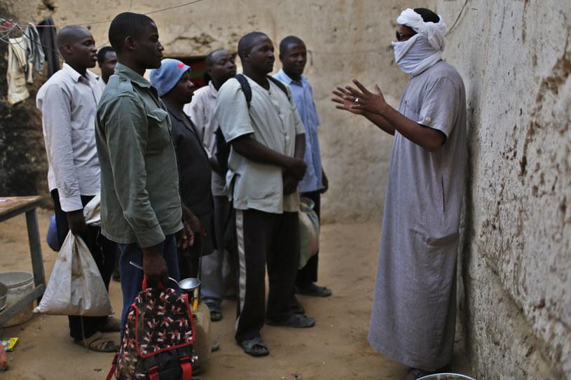 Mężczyzna z zakrytą twarzą to przemytnik. Rozmawia z migrantami, których ma przewieźć przez Saharę do Libii /REUTERS/ Ahmed Jadalla /Agencja FORUM