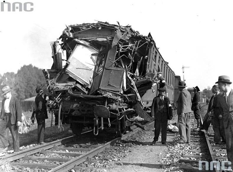 Mężczyźni przy zniszczonym wagonie kolejowym /Z archiwum Narodowego Archiwum Cyfrowego