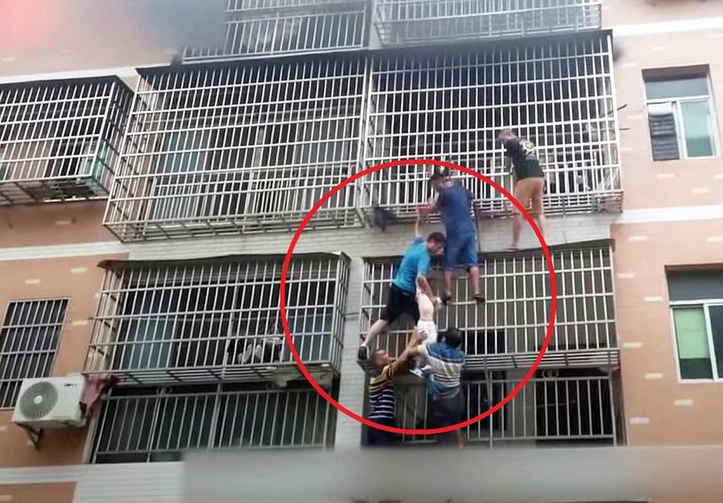 Mężczyźni uratowali dwie dziewczynki z pożaru mieszkania na trzecim piętrze w Yongzhou w Chinach /People's Daily, China /YouTube