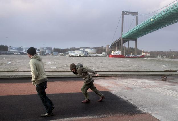 Mężczyźni walczą z silnym wiatrem /AFP